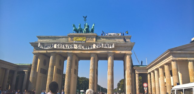 "Anti-Islam activists have staged an hour-long demonstration atop Berlin's Brandenburg Gate Saturday Aug. 27, 2016. The protesters unfurled a banner calling for ""secure borders"" in Germany. Police said 15 people were briefly detained over the protest and are likely to face charges of trespassing, harassment and breaching laws on public assembly Banner reads : Secure Borders - Secure Future."
