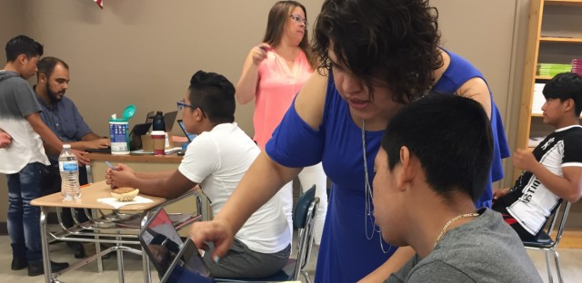 Fenton High School teacher Michelle Rodriguez helps a student create a presentation during a summer program for new migrant students at the suburban Bensenville high school.