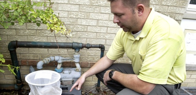 Andy Novinger, an assistant entomologist with the Northwest Mosquito Abatement District, explains how a gravid mosquito trap works at the district's facility in Wheeling, Ill., Thursday, May 29, 2003. The trap has a tub of stagnant water, which attracts female mosquitoes, and when the mosquitoes hover over the water, they are sucked into the trap by a battery-powered fan. The district has 14 of these traps set up in various residential areas to collect mosquitoes and test them for West Nile Virus and other mosquito-bourn illnesses.