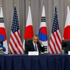 South Korean President Park Geun-hye, left, and President Barack Obama remove their ear pieces at the end of a meeting with Japanese Prime Minister Shinzo Abe, right, during the Nuclear Security Summit in Washington, Thursday, March 31, 2016.