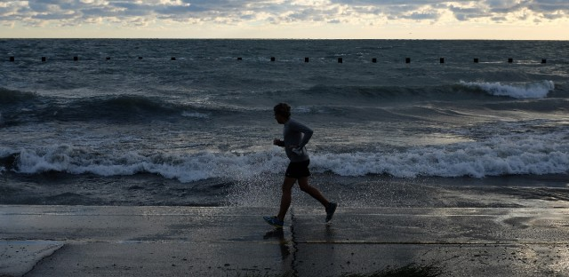 A runner cruises on a path as waves crash along the shore of Lake Michigan, Wednesday morning, Sept. 30, 2015, in Chicago.