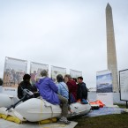 Visitors sit in an inflatable raft to get an idea of how thousands of refugees cross the Mediterranean Sea to Europe each year.