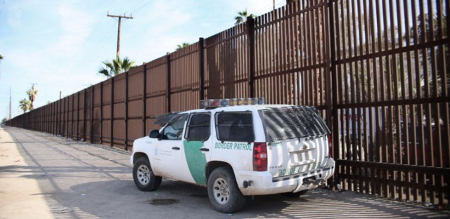 A Border Patrol agent looks over the U.S.-Mexico border wall in Calexico, Calif., on Jan. 31. Apprehensions at the southern border fell dramatically: from more than 40,000 per month late last year to 18,754 in February, and just 12,193 in March. (Sandy Huffaker/AFP/Getty Images)