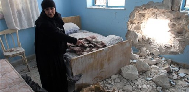 Sister Verona, the head of the Sednaya Covent, shows journalists a damaged room which was attacked by artillery fire, in Sednya north of Damascus, Syria on January 31, 2012. Christians, who make up about 10 percent of the population in Syria, say they are particularly vulnerable to the violence sweeping the country.