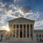 The sun flares in the camera lens as it rises behind the U.S. Supreme Court building in Washington, Sunday, June 25, 2017.