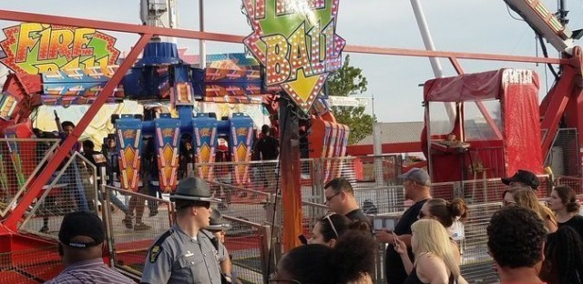 People watch as authorities respond after part of the Fire Ball ride broke off while in motion Wednesday night at the Ohio State Fair in Columbus, Ohio. One person was killed, and three were critically injured.