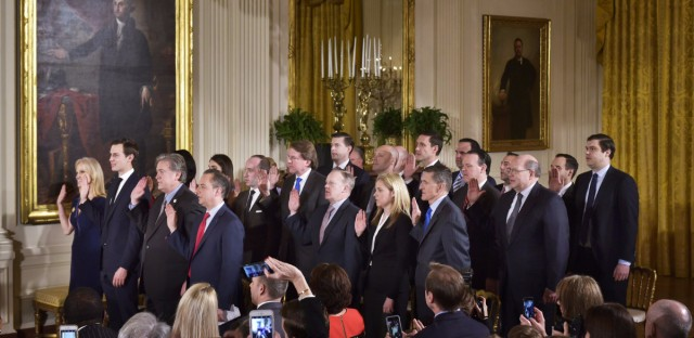 The White House senior staff is sworn in at the White House in January. Twenty-two members of the staff will make $179,700 this year and 18 more earn $165,000 a year, making the Trump administration's payroll top-heavy compared to the Obama administration.