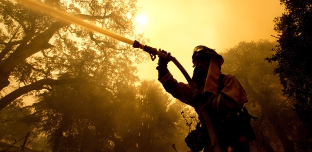 Napa County firefighter Jason Sheumann sprays water on a home as he battles flames from a wildfire on Monday in Napa, Calif. Wildfires whipped by powerful winds swept through Northern California sending residents on a headlong flight to safety through smoke and flames as homes burned.