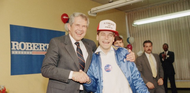 Then Democratic presidential candidate Pat Robertson shakes hands with Robert Sherman of the American Atheist Press at a rally for Robertson at an Oak Park, Illinois church in 1988.