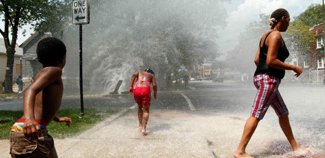 Children play in the spray of an open fire hydrant Chicago's south side in this 2012 photo.