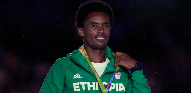 Ethiopia's silver medal winner Feyisa Lilesa poses during the medal ceremony for the men's marathon during the closing ceremony in the Maracana stadium at the 2016 Summer Olympics in Rio de Janeiro, Brazil, Sunday, Aug. 21, 2016.