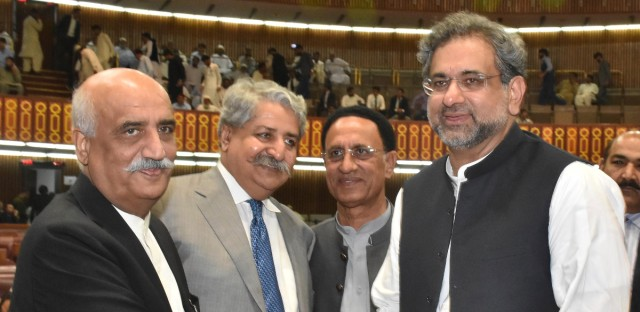 In this photo released by Pakistan's Press Information Department, newly-elected Prime Minister of Pakistan Shahid Khaqan Abbasi, right, is greeted by the Opposition leader Khursheed Shah, left, and others at the Parliament in Islamabad, Pakistan, Tuesday, Aug. 1, 2017. Pakistan's lower house of parliament elected Abbasi as the country's new prime minister, a loyalist of outgoing Nawaz Sharif, who was disqualified by the Supreme Court for concealing assets.(Pakistan Press Information Department via AP)