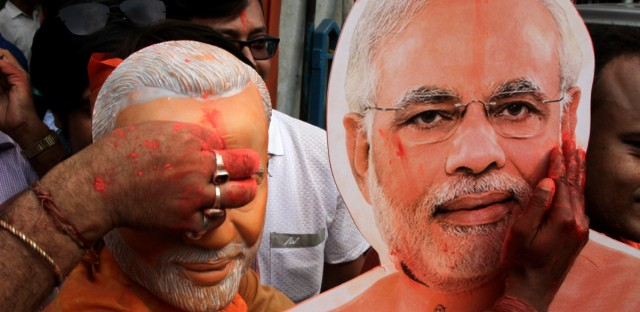 A Bharatiya Janata Party (BJP) supporter puts vermillion powder on a cutout of Narendra Modi during celebrations of the party's victory in Kolkata , India, Thursday, May 23, 2019. Indian Prime Minister Narendra Modi's party claimed it had won reelection with a commanding lead in Thursday's vote count, while the stock market soared in anticipation of another five-year term for the pro-business Hindu nationalist leader.