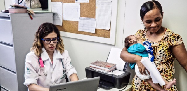 Dr. Danielle Cruz attends to 4-month-old Davi Lucas Francisca da Paz, held by his mother Eliane Francisca, in an examination room at the Institute of Integral Medicine Hospital in Recife, Brazil. Catherine Osborn/for NPR