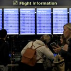 Travelers walk and check their flight information in Terminal 3 at Chicago's O'Hare International Airport in December. Nam Y. Huh/AP