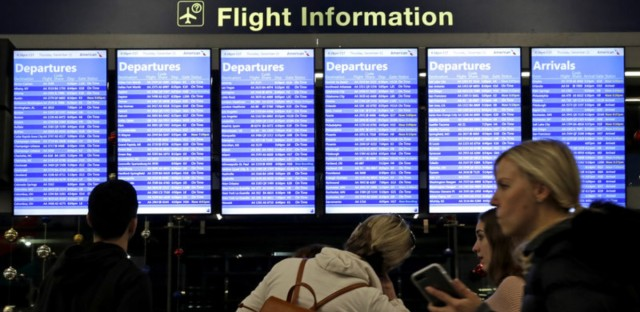 Travelers walk and check their flight information in Terminal 3 at Chicago's O'Hare International Airport in December. (Nam Y. Huh/AP)