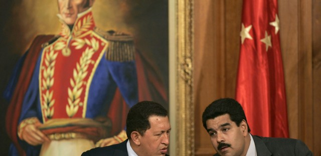 The late President Hugo Chávez and the now Acting President Nicolás Maduro confer under a portrait of Latin American hero Simón Bolivar.