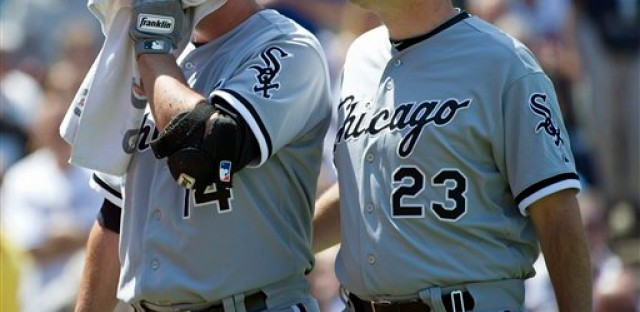 After being hit in the face, Paul Konerko walks off the field with manager Robin Ventura.