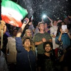 A group of jubilant Iranians cheer and spray artificial snow during street celebrations following a landmark nuclear deal, in Tehran, Iran, Tuesday, July 14, 2015. After long, fractious negotiations, world powers and Iran struck an historic deal Tuesday to curb Iran's nuclear program in exchange for billions of dollars in relief from international sanctions - an agreement aimed at averting the threat of a nuclear-armed Iran and another U.S. military intervention in the Middle East.