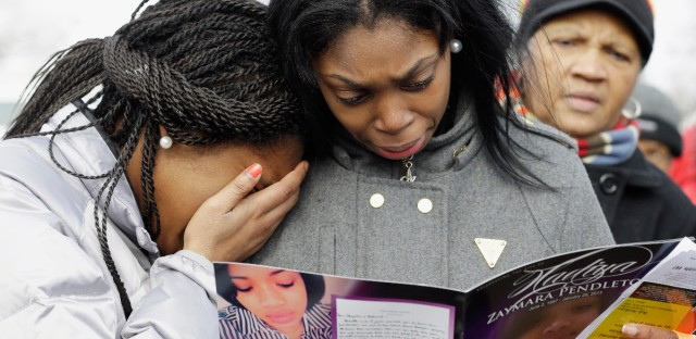In this Feb. 9, 2013 file photo, Danyia Bell, 16, left, and Artureana Terrell, 16, react as they read a program after the funeral service for 15-year-old Hadiya Pendleton outside the Greater Harvest Missionary Baptist Church in Chicago. Hundreds of mourners and dignitaries including first lady Michelle Obama packed the funeral service for the Chicago teen whose killing catapulted her into the nation's debate over gun violence. Since her death, the number of homicides and other violent crimes that turned Chicago into a national symbol of gun violence have fallen sharply after the city and police changed strategies.