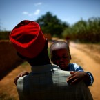 Ado Ibrahim carries his son Aminu through a village in northern Nigeria. Aminu was paralyzed by polio in 2012.