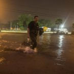 Lanny Dean takes video as he wades along a flooded Beach Boulevard next to Harrah's Casino as the eye of Nate pushes ashore in Biloxi, Miss., early Sunday.