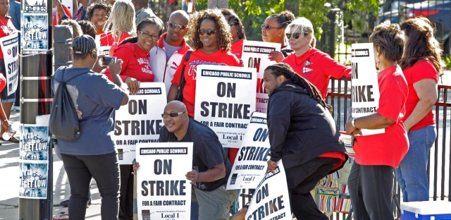 Chicago public school teachers take a group picture as they walk a picket line outside a school in Chicago.