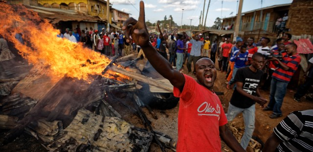 An opposition supporter yells in front of a burning barricade built from material looted from the property of a man of the Kikuyu tribe, that they broke into in the Kawangware slum of Nairobi, Kenya Friday, Oct. 27, 2017.