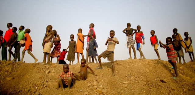 Children stand on top of an earthen dam in the camp in Bentiu. Massive dams, drainage canals and water retention pools were constructed after the camp flooded repeatedly during the rainy season. Residents say the water and mud was so deep in their huts that they had to sleep sitting up in chairs.