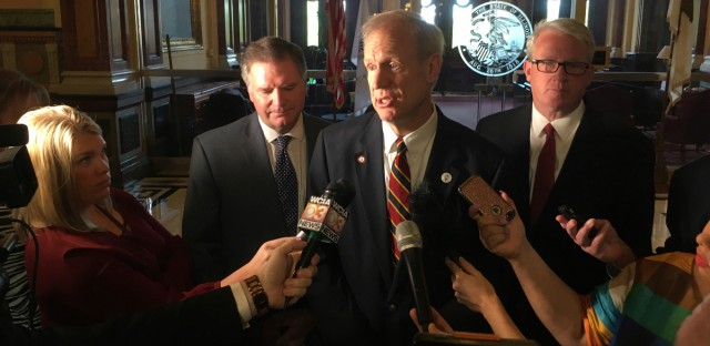 Gov. Bruce Rauner, center, addresses reporters outside his state Capitol office Tuesday, May 8, 2018. Rauner, a Republican, and the GOP legislative leaders want Democrats to reach agreement with them on a state budget plan before the May 31 scheduled adjournment of the Legislature.
