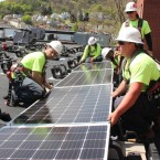 A work crew for the Pittsburgh company Energy Independent Solutions installs solar panels at a community building in Millvale, Pa.