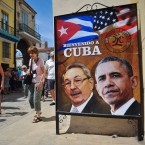 Tourists walk next to a poster of Cuban President Raul Castro and President Obama ahead of the U.S. leader's visit. Yamil Lage/AFP/Getty Images