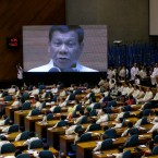 An image of Philippine President Rodrigo Duterte is seen on an electronic board during his second state of the nation address at the House of Representatives in suburban Quezon city, north of Manila, Philippines, Monday July 24, 2017. Duterte said he will not stop his deadly crackdown on illegal drugs and warns that addicts and dealers have two choices: jail or hell.