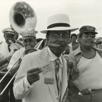 Sporting a plastic cigar in his mouth, Danny Barker leads the Onward Brass Band in a parade at the 1974 New Orleans Jazz and Heritage Festival.