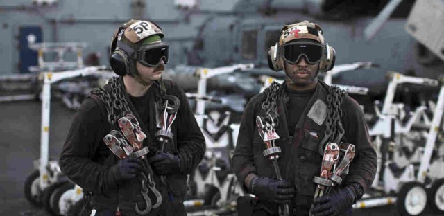 U.S. Navy air wing plane captains carry chains as they pause on the flight deck of the USS Theodore Roosevelt aircraft carrier last September. Every day, the steam-powered catapult aboard this massive aircraft carrier flings American fighter jets into the sky, on missions to target the extremist Islamic State group in Iraq and Syria.