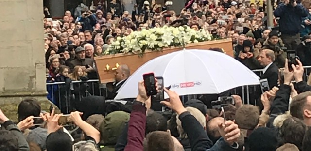 Nikos Orginos, 14, of Williamsburg, Va., teetered on a metal police railing to capture this view of Stephen Hawking's coffin as it left Cambridge University's church of St. Mary the Great.
