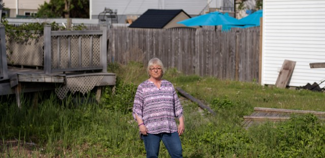 Like many other homeowners, Ann Marie Cianci — standing near her abandoned house on Staten Island, N.Y. — has been unable to move back home. After paying flood insurance for 32 years, she received only $60,000 out of her $250,000 policy.