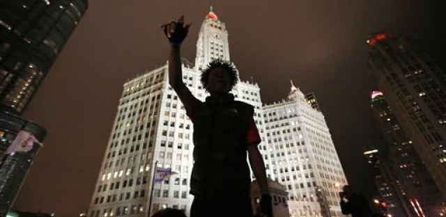 File: A protester is silhouetted against Chicago's famed Wrigley Building as he directs others to shutdown traffic on both sides of the Michigan Ave. bridge over the Chicago River, Wednesday, Nov. 25, 2015, one day after murder charges were brought against police officer Jason Van Dyke in the killing of 17-year-old Laquan McDonald.