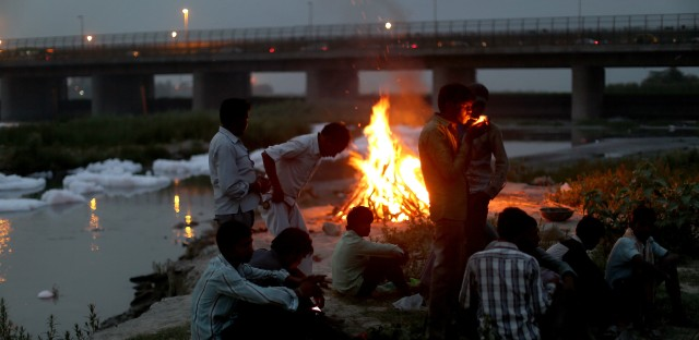 """Men watch the fires of a cremation along the banks of the Yamuna River against the backdrop of the Wazirabad Barrage and floating industrial waste. From the story """"Can India's Sacred But 'Dead' Yamuna River Be Saved,"""" 2016."""