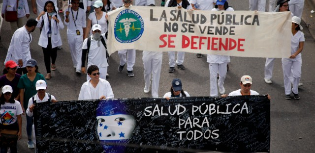 "Demonstrators march during a protest against the government of Honduras' President Juan Orlando Hernandez in Tegucigalpa, Honduras, Thursday, May 30, 2019. Thousands of doctors and teachers have been marching through the streets of Honduras' capital for the last three weeks, against presidential decrees they say would lead to massive public sector layoffs. The banners carried by the demonstrators read in Spanish "" Public health for all"" and ""Public health is not for sale. We will defend it."""