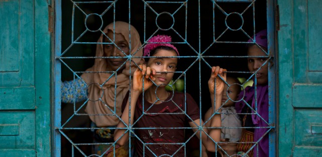 Newly arrived Rohingya Muslims from Myanmar look out from a madrasa window that they used as a shelter in Shahparirdwip, Bangladesh on Monday, Oct. 2, 2017.