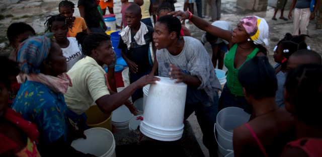 Residents argue while they wait to collect water to be used for cleaning or cooking at the Cite Soleil slum in Port-au-Prince, Haiti in November 2010. (AP Photo/Ramon Espinosa)