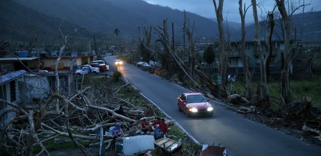 In this Sept. 26, 2017 photo, neighbors sit on a couch outside their destroyed homes as sun sets in the aftermath of Hurricane Maria, in Yabucoa, Puerto Rico.