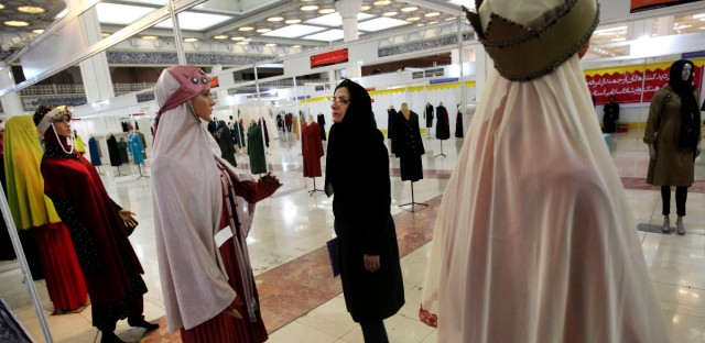 "An Iranian woman looks at outfits on mannequins, during the ""Second Fadjr International Fashion and Clothing Festival"" at the Imam Khomeini grand mosque, in Tehran, Iran, Monday, March 4, 2013. Iran's strict Islamic dress code for women, enforced after 1979 Islamic Revolution, requires them to cover their hair and bodies in public."