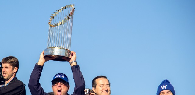 Tom Ricketts hoists the World Series trophy during the Chicago Cubs' victory parade.