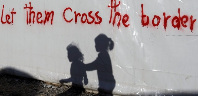 Shadows of children are cast on a tent bearing graffiti at the northern Greek border point of Idomeni, Greece, Wednesday, May 4, 2016. European Union countries that refuse to accept refugees under proposals to overhaul the EU's failed asylum laws could face large fines for each asylum seeker rejected.