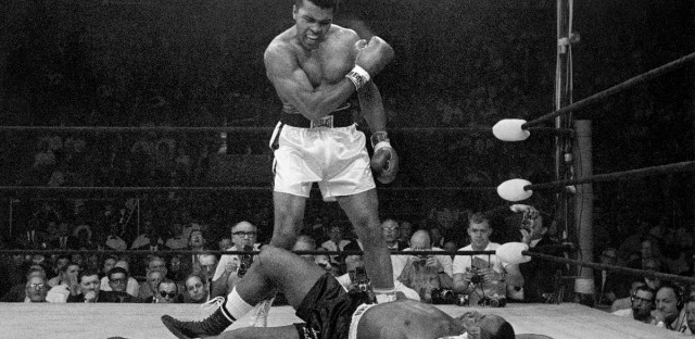 Heavyweight champion Muhammad Ali stands over fallen challenger Sonny Liston in Lewiston, Maine on May 25, 1965.