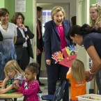 Hillary Clinton reacts as a 3-year-old presents her with her artwork at Lee Highway KinderCare in Fairfax, Va.