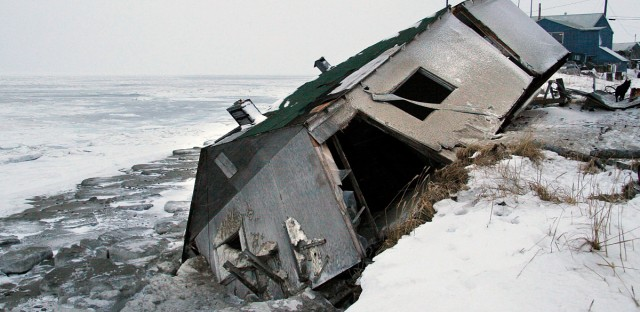 In this file photo from December 2006, Nathan Weyiouanna's abandoned house at the west end of Shishmaref, Alaska, sits on the beach after sliding off during a fall storm in 2005. In a special election held on August 16, 2016, the community voted to relocate.