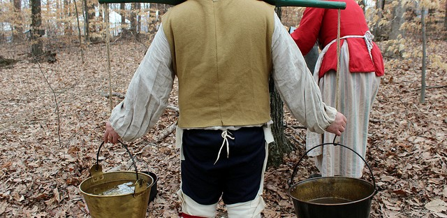 French camp settlers with maple sap buckets at National Maple Syrup Festival on Burton's Maplewood Farm in Medora, Indiana